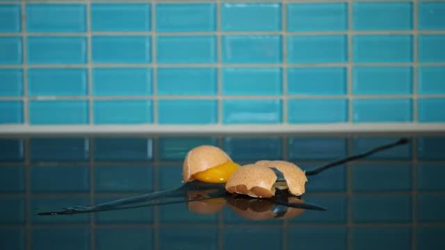 brown egg falling down and cracks open - uovo alimento di base video stock e b–roll