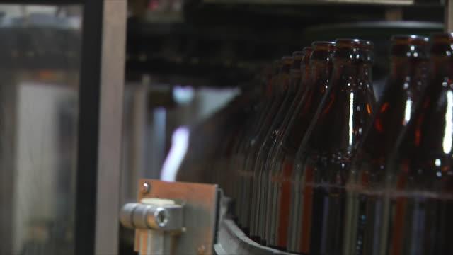 CU R/ F Brown glass beer bottles on conveyor / Wau, Western Bahr el Ghazal, Sudan