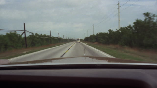 ms pov brown lincoln chasing white porsche on two lane highway  - two lane highway stock videos and b-roll footage