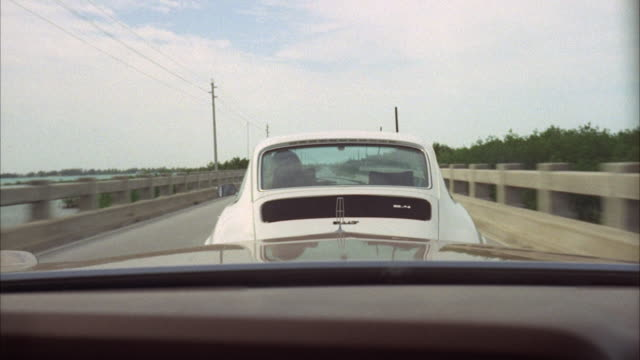 ms pov brown lincoln chasing white porsche on two lane highway  - following moving activity stock videos and b-roll footage