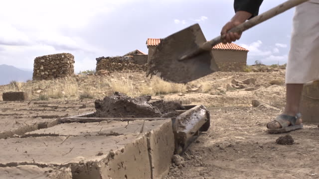 brown man mixes soil with water in a rectangular mold to form adobes - mud stock videos & royalty-free footage