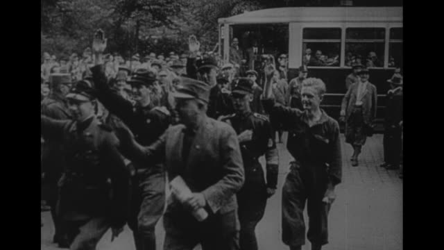 brown shirt escorts man from church / cu smiling man in formal suit gives nazi salute / nazi officials walking into building all give nazi salute to... - ナチズム点の映像素材/bロール