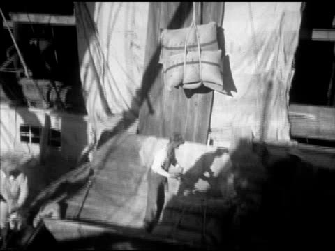 Brown skin men dock workers guiding bundled bags of sugar up onto ship unseen crane lifting bundled bags VS Warehouse w/ stacked bags men moving sack...