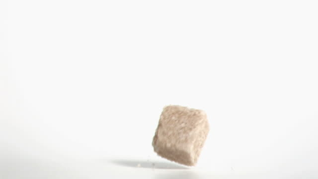 brown sugar cube falling in super slow motion - sugar cube stock videos & royalty-free footage