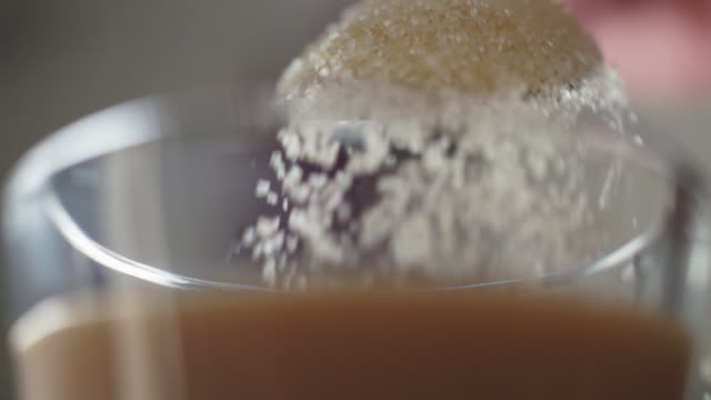 ecu slo mo brown sugar falling into mug of tea from teaspoon/ johannesburg/ south africa - teaspoon stock videos and b-roll footage