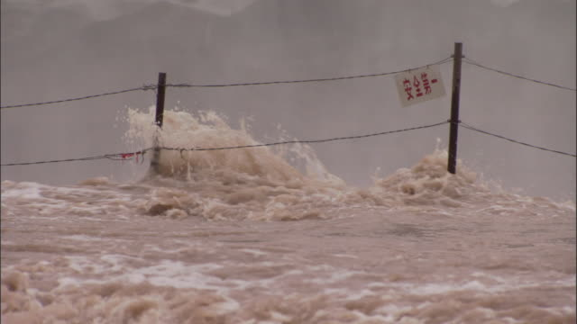 Brown water floods through fence with sign on, Hukou Falls