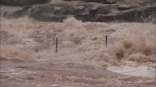 brown water floods through fence with warning sign on, hukou falls - brown stock videos & royalty-free footage