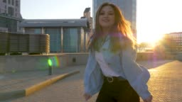 brown-haired woman with long hair dances against the backdrop of a sunset