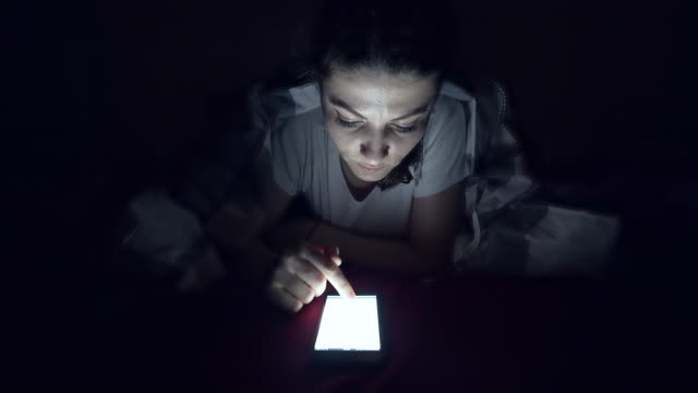 Browsing smart phone late in night.