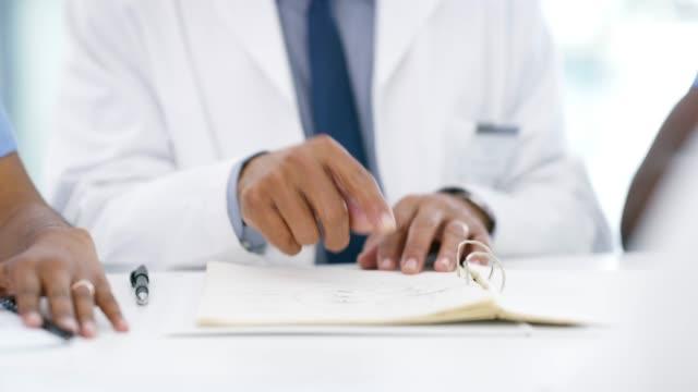 vídeos de stock e filmes b-roll de browsing through a patient's medical history - employee