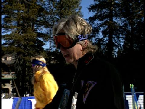 vídeos de stock e filmes b-roll de bruce davidson stands on ski slope waiting to ski as organizer gives instructions - bastão de esqui