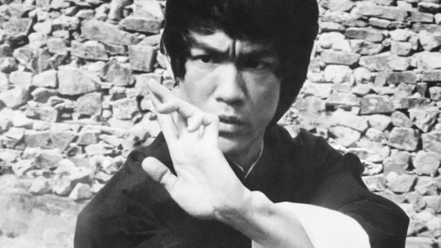 bruce lee practices martial arts near a stone wall. - martial arts stock videos & royalty-free footage