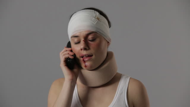 CU, TU, Bruised woman with bandaged head and neck brace on phone