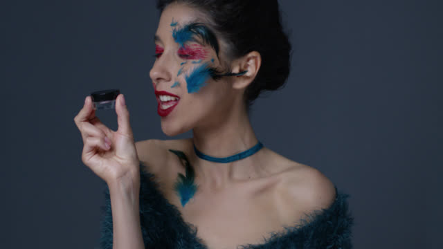 brunette fashion model in bright stage make-up and feathers holds eyeshadow jar and kisses it. fashion video. - lip liner stock videos & royalty-free footage