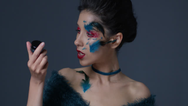 brunette fashion model in bright stage make-up and feathers holds eyeshadow jar. fashion video. - greasepaint stock videos and b-roll footage