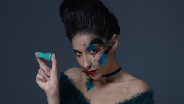 brunette fashion model in bright stage make-up and feathers holds nail polish bottle. fashion video. - greasepaint stock videos and b-roll footage
