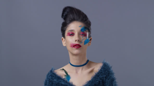 brunette fashion model in bright stage make-up and feathers shows facial expressions. fashion video. - haute couture stock videos and b-roll footage