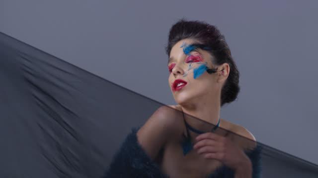 brünette mode-modell in hellen bühne make-up und federn zeigt mimik. mode-video. - halsreif stock-videos und b-roll-filmmaterial