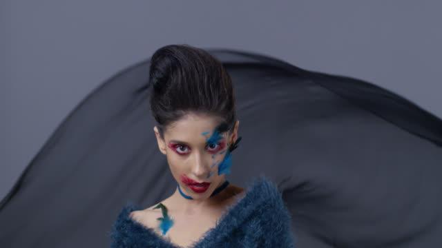 vidéos et rushes de brune mannequin en maquillage de scène lumineux et plumes montre les expressions faciales. mode vidéo. - rouge à lèvres rouge