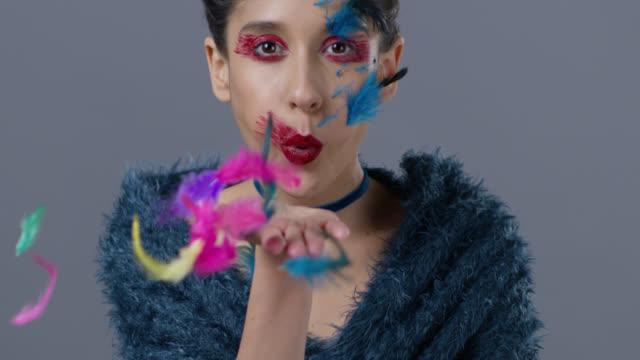 Brünette Mode-Modell in Bühne Make-up bläst Feder aus der Hand.  Mode-Video.