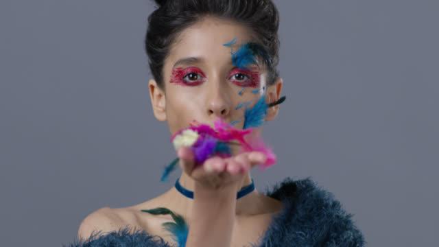brünette mode-modell in bühne make-up bläst feder aus der hand.  mode-video. - halsreif stock-videos und b-roll-filmmaterial