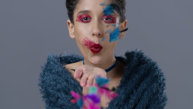 Brunette fashion model in stage make-up blows feather from her hand.  Fashion Video.