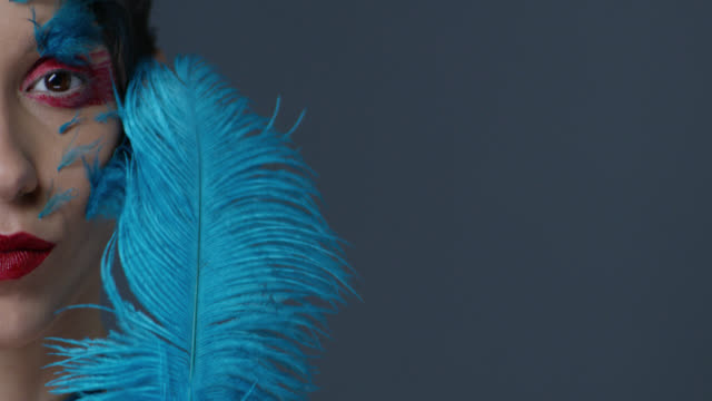 brunette fashion model in stage make-up touches her skin with blue ostrich feather. fashion video. - greasepaint stock videos and b-roll footage