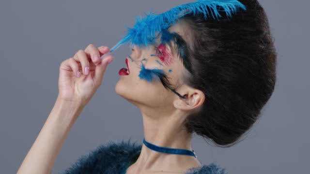 Brünette Mode-Modell in Bühne Make-up berührt ihre Haut mit blauer Straußenfeder. Mode-Video.