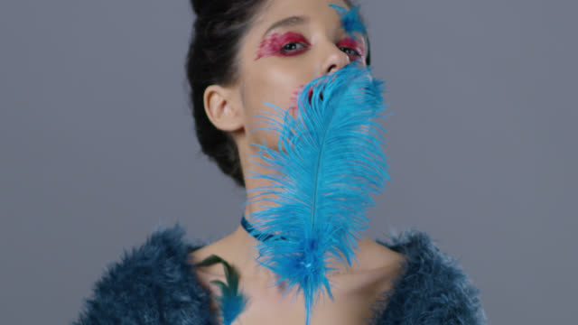 Brunette fashion model in stage make-up touches her skin with blue ostrich feather. Fashion Video.