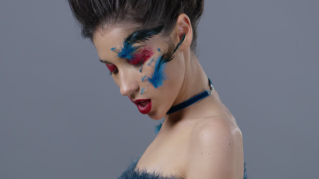 brunette fashion model in stage make-up touches her skin with blue ostrich feather. fashion video. - lip liner stock videos & royalty-free footage