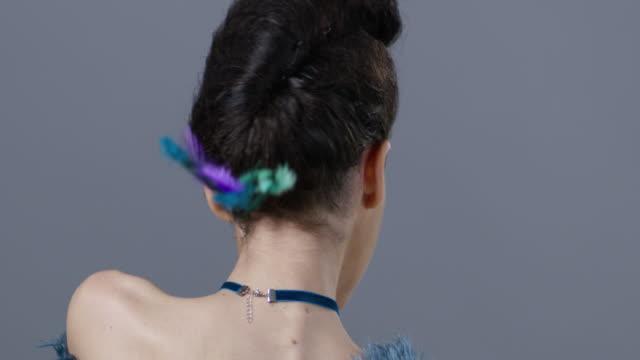 Brünette Fotomodell in Bühne Make-up Kurven und zeigt blaue Straußenfedern. Mode-Video.