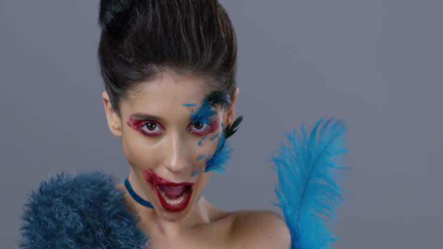 Brünette Mode-Modell in Bühne Make-up und zeigt blauen Strauß Feder, küssen. Mode-Video.
