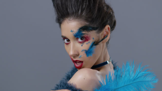 Brunette fashion model in stage make-up turns and shows blue ostrich feather. Fashion Video.