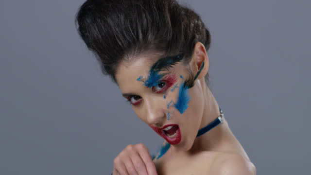 Brunette fashion model in stage make-up turns and shows blue ostrich feather, hisses. Fashion Video.