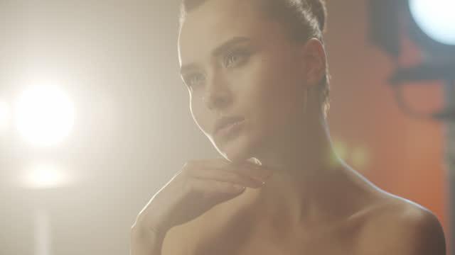 brunett flicka skådespelerska med vacker ögon make-up i starkt ljus, rör sig långsamt, rör vid hennes ansikte med handen och ser rakt framåt. - skådespelerska bildbanksvideor och videomaterial från bakom kulisserna