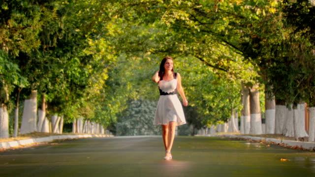 vídeos de stock, filmes e b-roll de menina morena de vestido preto e branco andando beco em direção à câmera - mulher bonita