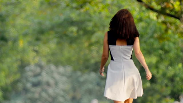brunette girl in black and white dress walking along alley - white dress stock videos & royalty-free footage