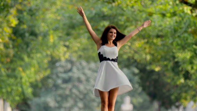 Brunette girl in dress swirling happily in park with her hands in air