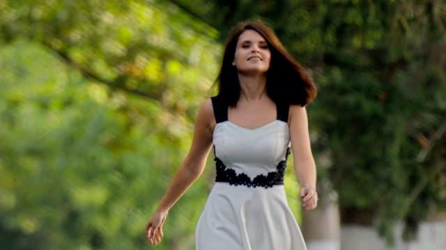 Brunette girl in dress walking along alley towards camera
