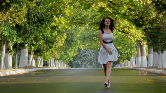 brunette girl in dress walking in park on suny day - skipping along stock videos & royalty-free footage