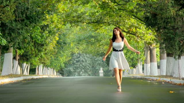 vídeos de stock, filmes e b-roll de menina morena vestido caminhando em direção a câmera ao longo beco do parque - redemoinho