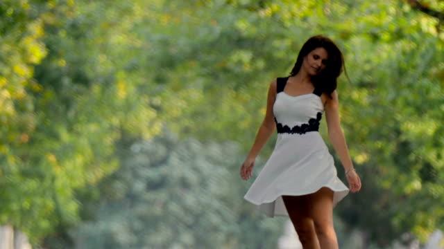vídeos de stock, filmes e b-roll de menina morena vestido caminhando em direção a câmera rodopiando alegremente a caminho - redemoinho