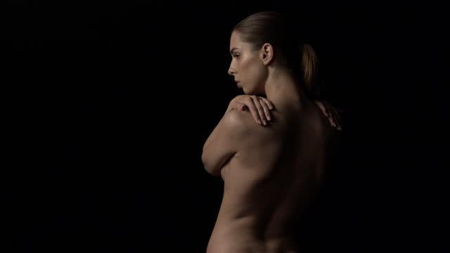 stockvideo's en b-roll-footage met brunette meisje naakt, draait haar hoofd - uitzicht vanaf de achterkant. - rug