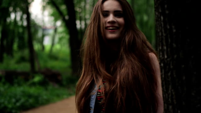 brunette girl peeps round tree trunk. - hide and seek stock videos and b-roll footage