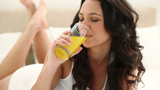 brunette haired woman drinking orange juice - orange juice stock videos and b-roll footage