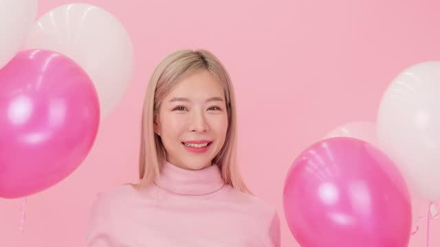 vídeos de stock, filmes e b-roll de morena feliz dança com balões no fundo rosa. - fundo rosa