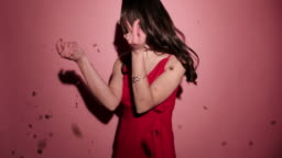 Brunette happy woman laughing with confetti in pink background wear red dress