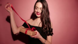 Brunette happy woman open her present with confetti in pink background wear black dress