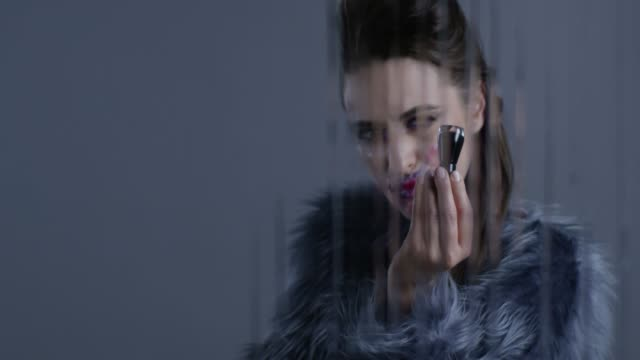 vídeos y material grabado en eventos de stock de modelo morena alta moda en piel sostiene botella de esmalte de uñas negro. video de la moda. - articulación humana