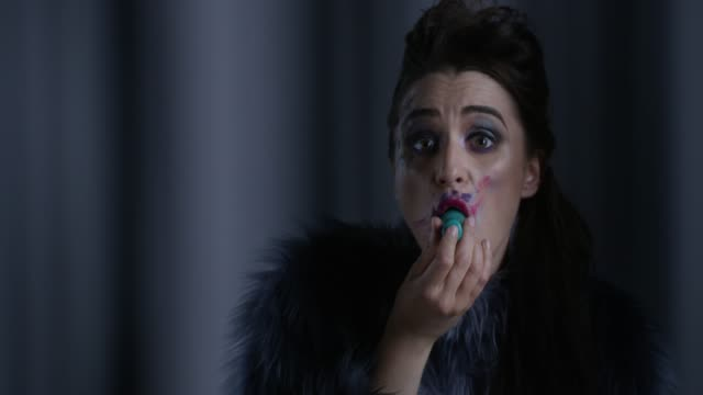 brunette high fashion model in fur vomits with turquoise colored nail polish bottle. fashion video. - nail varnish stock videos and b-roll footage